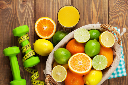 sport background: Citrus fruits in basket and dumbells. Oranges, limes and lemons. Over wood table background