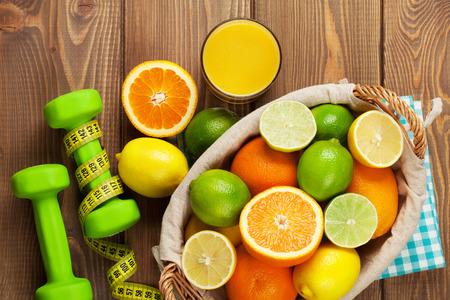 salud y deporte: Las frutas c�tricas en la cesta y mancuernas. Las naranjas, limas y limones. Sobre la mesa de madera de fondo