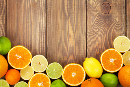 natural juices: Citrus fruits. Oranges, limes and lemons. Top view over wooden table background with copy space Stock Photo