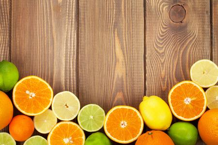 fruta tropical: Las frutas c�tricas. Las naranjas, limas y limones. Vista superior sobre fondo de la tabla de madera con espacio de copia