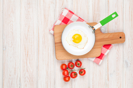 Healthy breakfast with fried egg and tomatoes on white wooden table with copy space