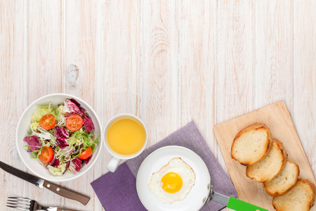 Healthy breakfast with fried egg, toasts and salad on white wooden table with copy space 版權商用圖片