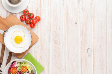 卵焼き、トマト、コピー スペースを持つ白い木製テーブルにサラダと健康的な朝食