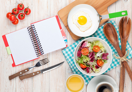 Healthy breakfast with fried egg, toasts and salad on white wooden table with notepad for copy space photo