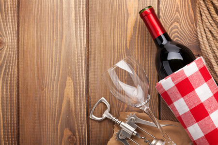 brown bottle: Red wine bottle, wine glass and corkscrew on wooden table background with copy space