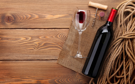 wine bottle: Red wine bottle, wine glass and corkscrew on wooden table background with copy space