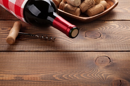 drink bottle: Red wine bottle, corks and corkscrew on wooden table background with copy space Stock Photo