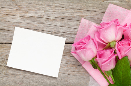 garden table: Pink roses bouquet and blank greeting card over wooden table. Top view with copy space