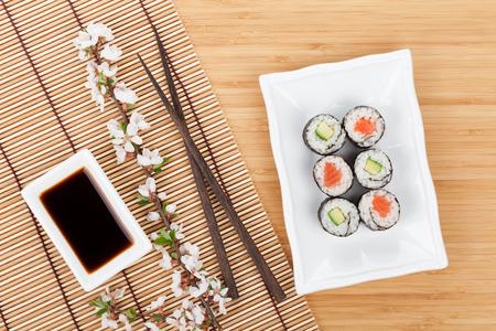 Sushi maki set and sakura branch on bamboo table photo