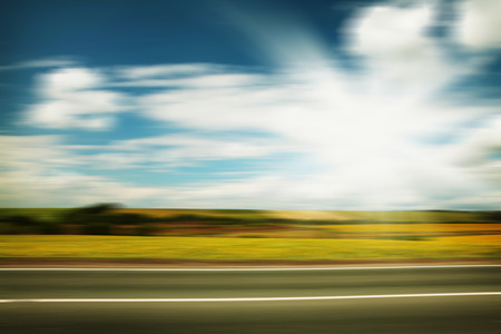 street view: Road through the yellow sunflower field with clouds on blue sky motion blur