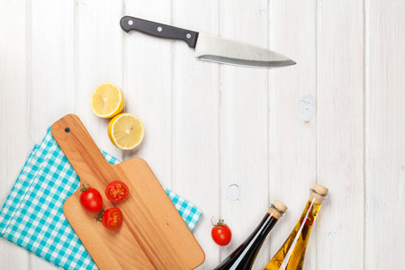 cutting vegetables: Cooking with tomatoes and lemons. View from above over white wooden table