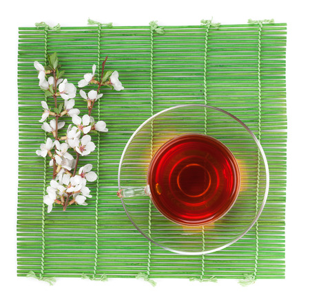 Japanese green tea and sakura branch over bamboo mat. Isolated on white background photo