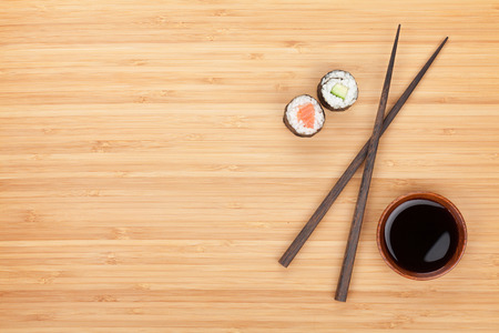 maki sushi: Maki sushi, chopsticks and soy sauce on bamboo wooden table background with copy space