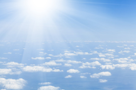 to white: Blue sky with clouds and sun. View from airplane Stock Photo