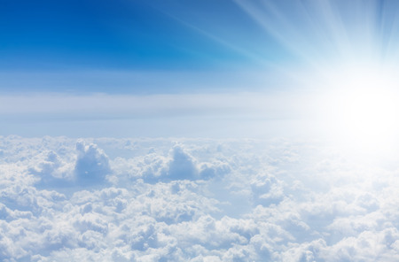 fluffy clouds: Blue sky with clouds and sun. View from airplane Stock Photo
