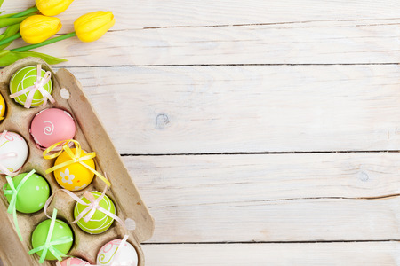 Easter background with colorful eggs and yellow tulips over white wood. Top view with copy space