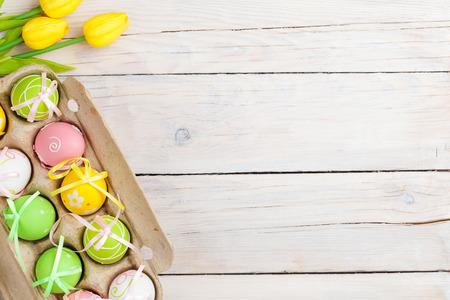 huevo blanco: Fondo de Pascua con huevos de colores y tulipanes amarillos sobre madera blanca. Vista superior con espacio de copia