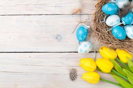 pascuas navide�as: Fondo de Pascua con huevos de colores y tulipanes amarillos sobre madera blanca. Vista superior con espacio de copia