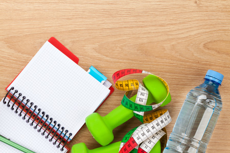 Dumbells, tape measure, water bottle and notepad for copy space. Fitness and health photo