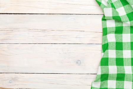 checkered background: Green towel over wooden kitchen table. View from above with copy space