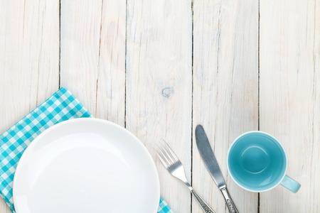 Platte Leer, Becher und Besteck auf weißen Holztisch Hintergrund. Blick von oben mit Kopie Raum
