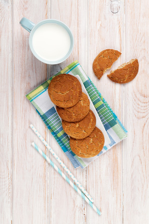 milk and cookies: Cup of milk and gingerbread cookies on white wooden table Stock Photo