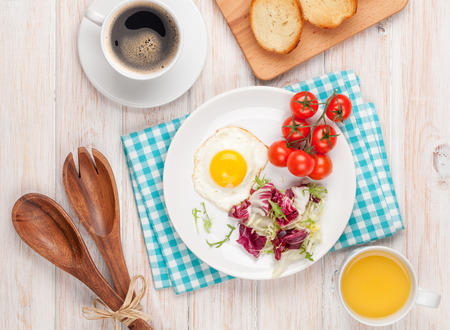 english breakfast: Healthy breakfast with fried egg, toasts and salad on white wooden table