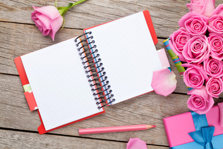 Blank notepad and gift box full of pink roses over wooden table. Top view with copy space