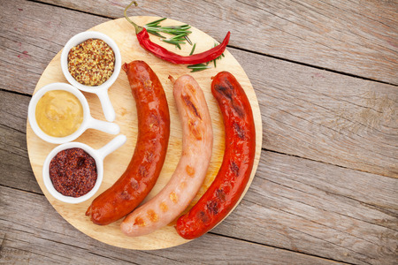 Various grilled sausages with condiments on cutting board with copy space photo