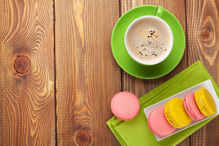Colorful macaron cookies and cup of coffee on wooden table background photo