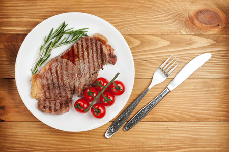 Sirloin steak with rosemary and cherry tomatoes on a plate. View from above