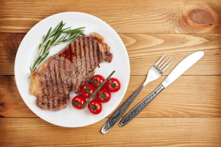 サーロイン ステーキ ローズマリーとチェリー トマトを皿。上からの眺め 写真素材