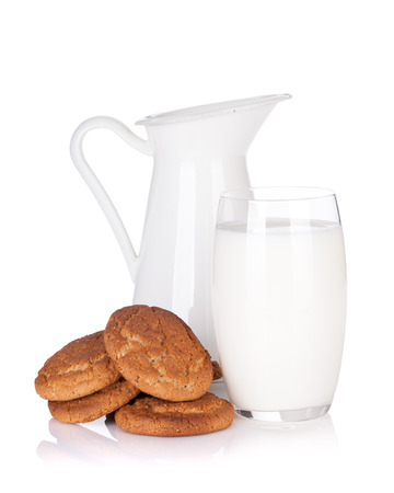 Milk jug, glass and cookies. Isolated on white background photo