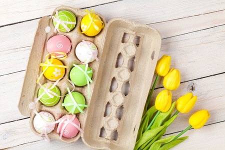 Easter background with colorful eggs and yellow tulips over white wood. Top view photo