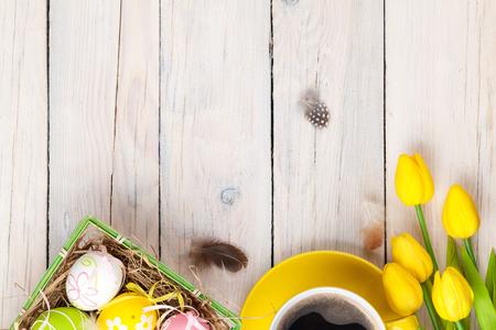 Pasen achtergrond met kleurrijke eieren en gele tulpen op wit hout. Bovenaanzicht met een kopie ruimte Stockfoto