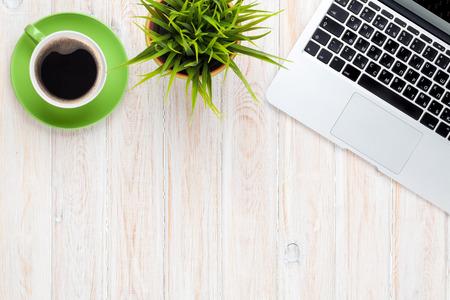 Kancelářský stůl stolu s přenosným počítačem, šálek kávy a květiny. Pohled shora s kopií vesmíru