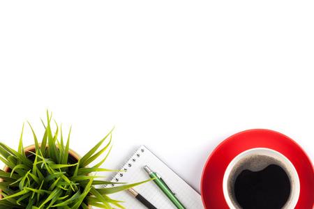 Kancelářský stůl stůl se zásobami, šálek kávy a květiny. Samostatný na bílém pozadí. Pohled shora s kopií vesmíru Reklamní fotografie