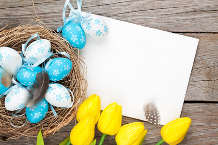 Easter greeting card with blue and white eggs and yellow tulips over wood. Top view with copy space photo