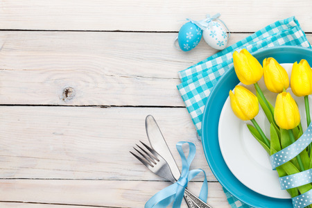 Easter background with yellow tulips and colorful eggs over white wooden table. Top view with copy space photo