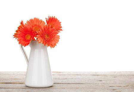 dalia: Flores de gerbera naranja en el lanzador en la mesa de madera. Aislado en el fondo blanco Foto de archivo
