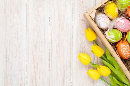huevo: Fondo de Pascua con huevos de colores y tulipanes amarillos sobre madera blanca. Vista superior con espacio de copia