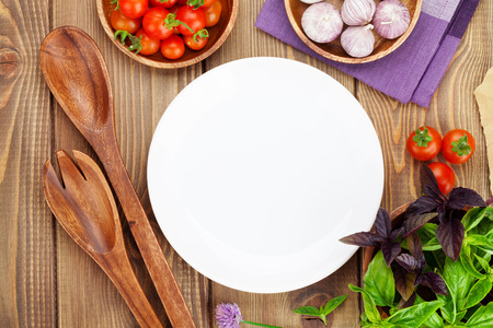 Fresh farmers tomatoes and basil on wood table with empty plate for copy space Stock Photo
