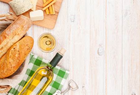 pan y vino: Vino blanco, queso y pan en blanco de madera fondo de la tabla. Vista superior con espacio de copia