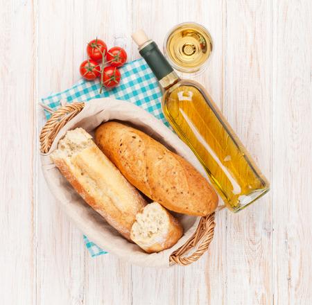 pan y vino: El vino blanco y pan en la mesa de madera blanca