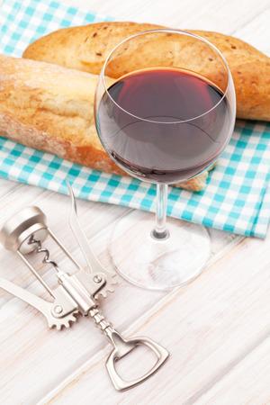 copa de vino: El vino tinto y pan en la mesa de madera blanca