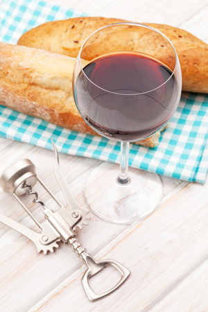wine glass: Red wine and bread on white wooden table
