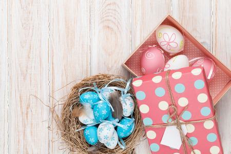 easter nest: Easter with blue and white eggs in nest and gift box over white wood. Top view with copy space