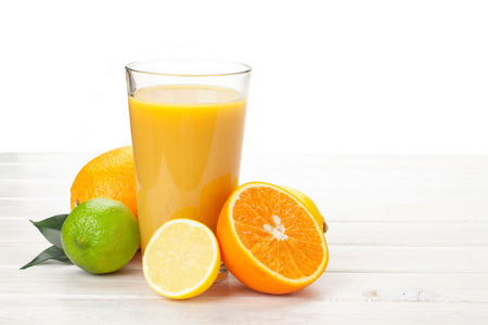 glass table: Orange juice and citrus fruits on white wooden table Stock Photo