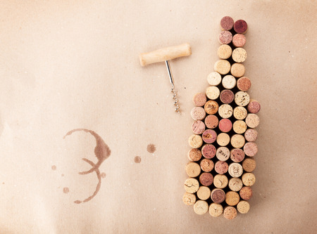 bottle of wine: Wine bottle shaped corks and corkscrew over cardboard . Top view with copy space