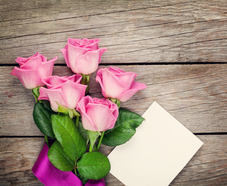 decoration: Pink roses and valentines day blank greeting card or photo frame over wooden table. Top view with copy space